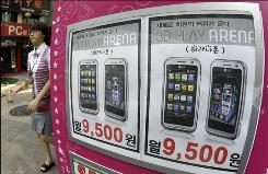 A South Korean woman walks near an advertisement for locally manufactured mobile phones, with similar features and looks to those of Apple Inc.'s iPhone,  in Seoul, South Korea, Wednesday, Sept. 23, 2009. South Korea's telecommunications regulator said Wednesday it has given approval for Apple's hit iPhone to be sold in the country.