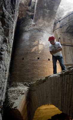 An unidentified man looks down in a recently unearthed brick structure incorporating a 4-meter diameter pillar, seen in the background, discovered during maintenance works in the Roman Forum in Rome. Archaeologists believe the structure supported a rotating dining room imitating the Earth's movement and used by Roman Emperor Nero to impress his guests in his Golden Palace.
