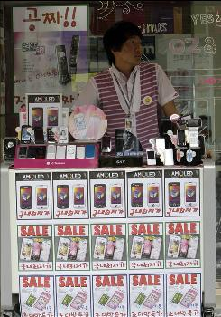 A street vendor waits for customers at a mobile phone shop in Seoul, South Korea, Wednesday, Sept. 23, 2009. The iPhone is expected to arrive in South Korea soon.