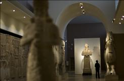 A journalist looks at an Assyrian statue, at Iraq's national museum, in Baghdad, on Tuesday, Nov. 24, 2009. Google is documenting the treasures of Iraq's national museum, home to priceless artifacts from the Stone Age through Islamic periods, and will make the photographs available online early next year, the company's chairman said Tuesday.