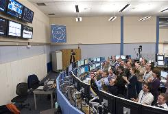 In this photo provided by the European Organization for Nuclear Research (CERN), scientists celebrate in the control room as the world's biggest atom-smasher, Large Hadron Collider (LHC), sets a world record by accelerating to energy levels that had never been previously reached.