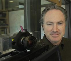 Eric Horvitz, former president of the Association for the Advancement of Artificial Intelligence, poses for a photo with a camera from a currently non-functioning computerized receptionist outside of his in his office at Microsoft in Redmond, Wash., where he works as a researcher.