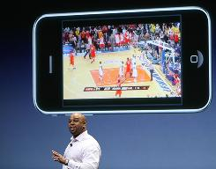 Oke Okara from ESPN demonstrates a new video feature for the iPhone during an Apple event earlier this year. Wireless data hogs who jam the airwaves by watching video on their iPhones will be put on tighter leashes, an AT&T exec says.