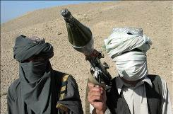 Face-covered militants who they say are Talibans pose with an RPG in Zabul province, southern of Kabul, Afghanistan Saturday, Oct. 7, 2006.