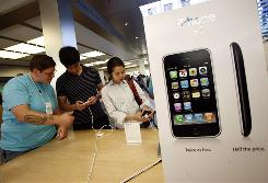Customers examine the iPhone 3G at the Apple Store in New York.
