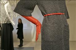 A mannequin wearing a red belt and elbow length red gloves frames a woman looking at fashions on display in Israeli-born designer Elie Tahari's showroom in New York, Thursday, Feb. 1, 2007.