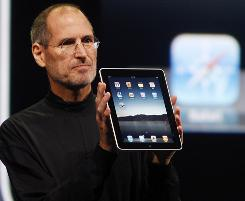 Apple CEO Steve Jobs shows off the new iPad during an event in San Francisco.