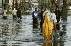 Sam Nixon walks through high water on Canal Street as he carries a dog he rescued 30 August 2005 in New Orleans after Hurricane Katrina.