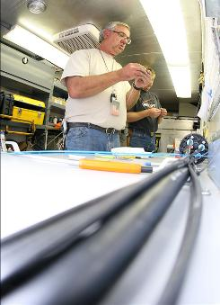 Verizon employee Larry Hames, with his partner David Fell behind him, splices the new fiber optic lines together in a Long Beach, CA neighborhood.