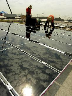 Workers install solar panels on a warehouse rooftop. Eventually there will be 33,700.