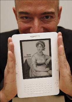 "Amazon CEO Jeff Bezos displays a Kindle during an interview in Cupertino, Calif. Bezos said a color version is ""still a long way out."""