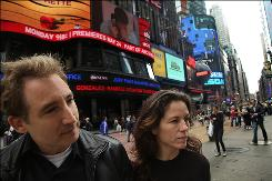 Brian Greene, a string theorist known for bringing his complex field of science to the masses, and Tracy Day, his wife and organizing partner behind World Science Festival, pose in Times Square, New York on May 19, 2010. This years World Science Festival begins June 2.