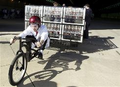 In this May 5 photo, Fritz Grobe pilots the Coke Zero & Mentos Rocket Car in its launch in Tustin, Calif. The contraption, created by Grobe and Stephen Voltz, of Buckfield, Maine, features a utility trailer on the back, a modified girl's bike on the front, and is powered using the fizzy reaction created by dropping Mentos into bottles of Coke Zero.