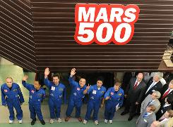 Members of the Mars 500 crew wave before being locked into the isolation facility in Moscow.
