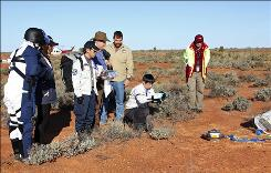 In this photo released by the Japan Aerospace Exploration Agency (JAXA), a technician takes photos of a sampler capsule that was detached from JAXA's Hayabusa probe in a desert in the Woomera Prohibited Area, southern Australia on June 14.