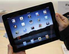 In this April 3, 2010 file photo, a customer uses an Apple iPad at an Apple store in San Francisco. Rev. Paolo Padrini, a consultant with the Vatican's Pontifical Council for Social Communications, has launched a free iPad app to replace the Roman missal.