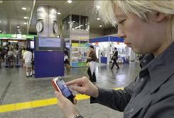 "Daisuke Tsuda tweets with his mobile phone at a station in Tokyo on June 14. Tsuda believes Japan is enjoying the ""richest and most varied form"" of Twitter."