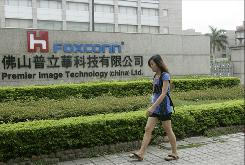 A Chinese worker walks past a Foxconn factory in an industrial district of Foshan City, southern China's Guangdong province in June 2010. Foxconn plans to shift part of its production to other parts of China as it faces rising labor costs following a run of suicides and wage hikes, and according to reports citing unnamed executives, Foxconn will move some manufacturing from Shenzhen to northern Tianjin and central Henan province.