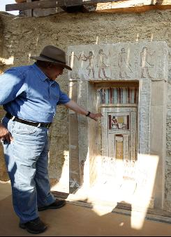 Egyptian Antiquities chief Zahi Hawass shows the false door of the unearthed tomb that belongs to Shendwas, the father of Khonsu, on Thursday, July 8, 2010. Both served as heads of the royal scribes during the Old Kingdom, in Saqqara near Cairo.