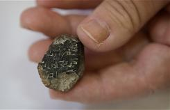Israeli archaeologist Eilat Mazar of the Hebrew University holds a 2-centimeter (0.8-inch) long fragment bearing an ancient form of writing known as Akkadian wedge script, in Jerusalem, Monday, July 12, 2010. Archaeologists say the newly discovered clay fragment dated to the 14th century B.C. is the oldest example of writing ever found in antiquity-rich Jerusalem.