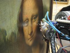This photo provided Friday July 23, 2010, by the National Center of Scientific Research shows the Mona Lisa painting being examined with a non-invasive technique called X-ray fluorescence spectroscopy to study the thickness of paint layers and their chemical composition.