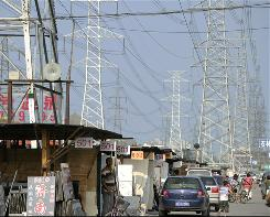 "Traffic passes below power lines in Beijing on July 20, 2010. China rejected an assessment from the International Energy Agency that it had surpassed the United States to become the world's top energy consumer, calling the data ""unreliable."""