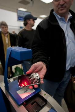 A Continental Airlines passenger scans his boarding pass on a Blackberry in Houston in February.