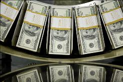 Stacks of one hundred dollar bills pass through a circulator machine at the Bureau of Engraving and Printing in Washington, D.C., U.S., on Wednesday, Oct. 14, 2009.