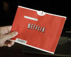 In this file photo made July 20, 2010, a Netflix customer holds up a movie in Palo Alto, Calif.