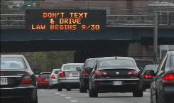 In this photo taken Friday, Sept. 24, 2010, a sign over the Massachusetts Turnpike in Boston alerts motorists to a new state law banning texting while driving.