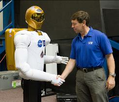 In this Aug. 4, 2010 picture provided by NASA, NASA astronaut Michael Barratt, STS-133 mission specialist, shakes hands with Robonaut 2 during a news conference at NASA's Johnson Space Center in Houston.