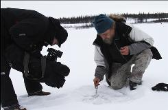 In this photo taken Oct. 23, 2010, Russian scientist Sergey Zimov demonstrates for AP Television News the emission of methane trapped under the ice of a Siberian lake near the town of Chersky, Russia.