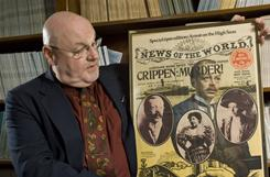 John Tretrail III holds up a copy of 'News of the World' from 1910 featuring the Crippen murder trial on the cover.