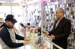 Ritmo Records owner Miguel Amador meets with customer Ramon Corona in one of his two stores in Camden, N.J. Five years ago, the majority of his revenue came from music CDs. Now his mobile device sales are up 50 percent from last year.