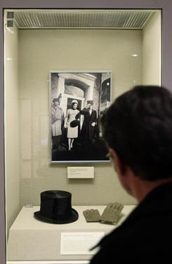 A visitor at the John F. Kennedy Library and Museum looks at the top hat and gloves Kennedy had made for his inauguration.