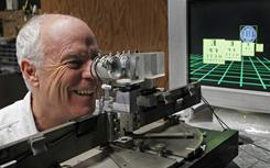 University of California at Berkeley Professor Marty Banks looks through a birefringent lens display in Berkeley, Calif. Powerful business interests are betting that 3-D will be the big new thing in entertainment, despite an important obstacle: today's technology still gives many people headaches.