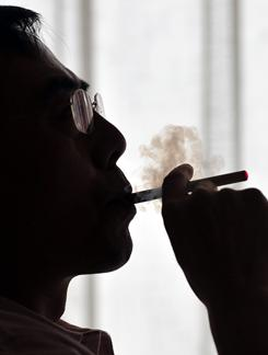 The inventor of the electronic cigarette, Hon Lik smokes his invention in a photo from 2009.