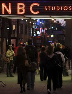 In this file photo, the NBC logo glows in neon lights at its headquarters in New York.