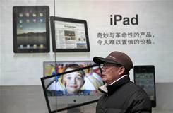 A man stands near an Apple' ad in Shanghai, China. Apple said its audits found a doubling in labor, safety and other abuses by its suppliers in 2010.