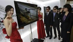 Models and LG Electronics employees wearing special glasses watch a Cinema 3-D TV by LG Electronics during a press unveiling in Seoul, South Korea.