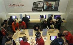 In this file photo, shoppers browse the MacBook Pro display at an Apple Store in San Francisco.
