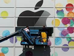 Workers apply the Apple logo the outside of the Yerba Buena Center for the Arts on Monday.