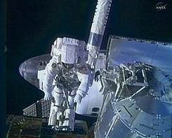 This NASA TV framegrab shows Discovery shuttle astronaut Steve Bowen on the end of the robotic arm during the first spacewalk on Monday.