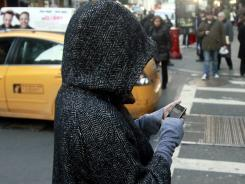 A  pedestrian uses a phone by a crosswalk in New York in January.