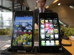 Samsung Electronics' Galaxy S, left, and Apple's iPhone 4 are displayed at the headquarters of South Korean mobile carrier KT in Seoul, South Korea, Friday, April 22, 2011.