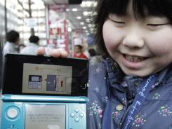 A young girl shows off Nintendo's newest computer game console, Nintendo 3DS in Tokyo.