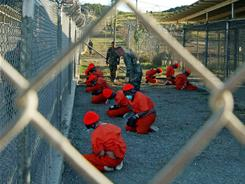In this handout photo from the Department of Defense from 2002, Taliban and al-Qaeda detainees in orange jumpsuits sit in a holding area at Camp X-Ray at Naval Base Guantanamo Bay, Cuba.