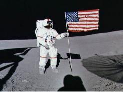 This 1971 photo shows astronaut Alan B. Shepard Jr,, Apollo 14 commander, standing by the U.S. flag on the lunar surface during the early moments of the first extra-vehicular activity of the mission.