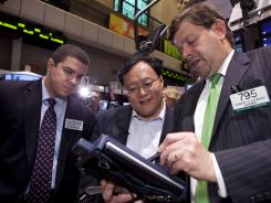 Joseph Chen, center, CEO of Renren, a Beijing-based social-networking website, meets with James Dipisa, left, and Edward Schreier at the New York Stock Exchange on the company's first day of trading.