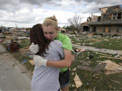 Mary Hoefflin, left, and Lauren Densic hug after a 2010 tornado struck Millbury, Ohio, in June 2010.